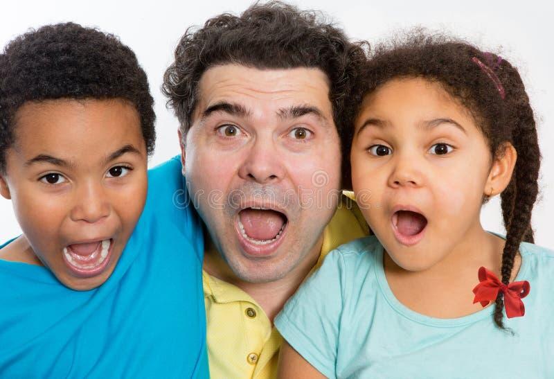 Papa et enfants étonnés avec la bouche grande ouverte photographie stock libre de droits