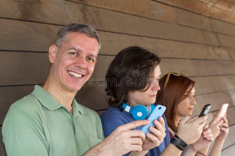 Papa et enfants : garçon et fille tenant le téléphone portable Jour de pères image libre de droits
