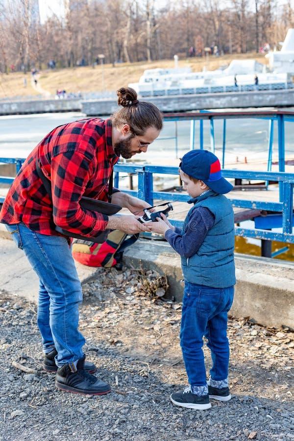 Papa et fils jouant avec le bourdon, l'homme et le garçon jouant avec le bourdon de vol en parc photographie stock libre de droits