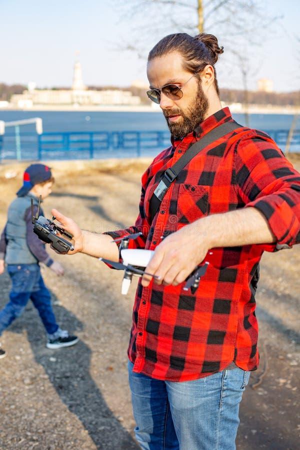 Papa et fils jouant avec le bourdon, l'homme et le garçon jouant avec le bourdon de vol en parc photos stock