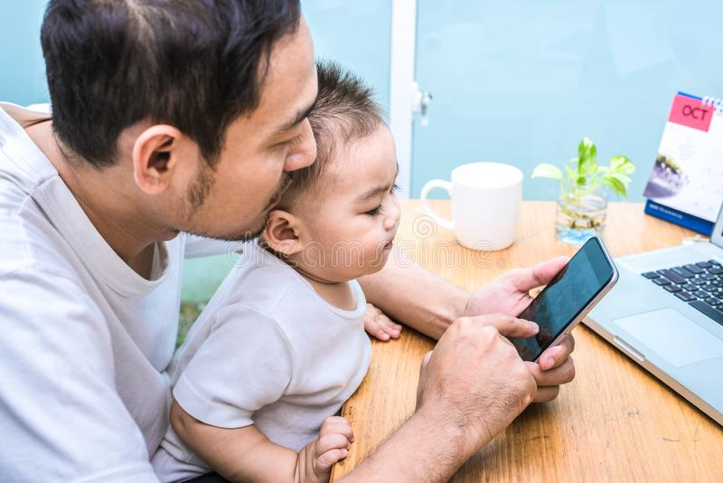 Papa et fils simples ? l'aide de l'ordinateur portable ensemble heureusement Concept de technologie et de modes de vie Thème heur photographie stock
