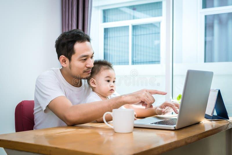 Papa et fils simples ? l'aide de l'ordinateur portable ensemble heureusement Concept de technologie et de modes de vie Thème heur photo stock