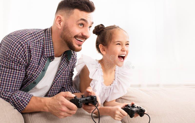Papa gai appréciant le jeu vidéo avec sa fille mignonne images stock