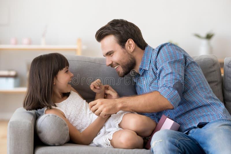 Papa heureux et jeu mignon de fille chatouillant ensemble sur le sofa photos libres de droits