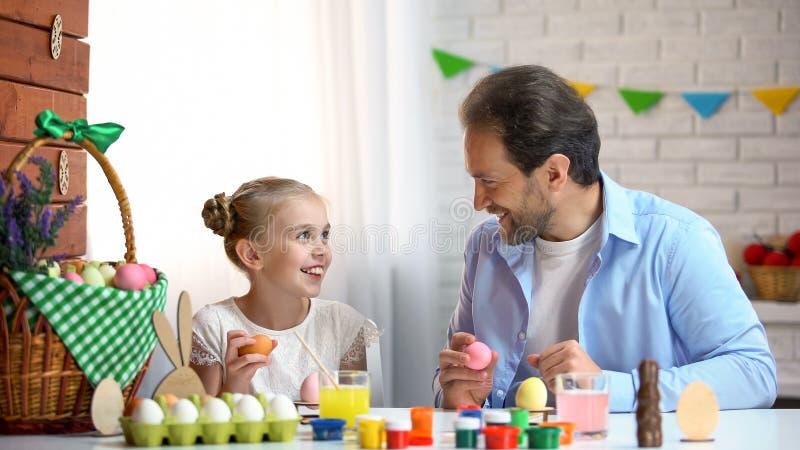 Papa heureux et petite fille regardant l'un l'autre, tenant des oeufs de pâques, ayant l'amusement images stock