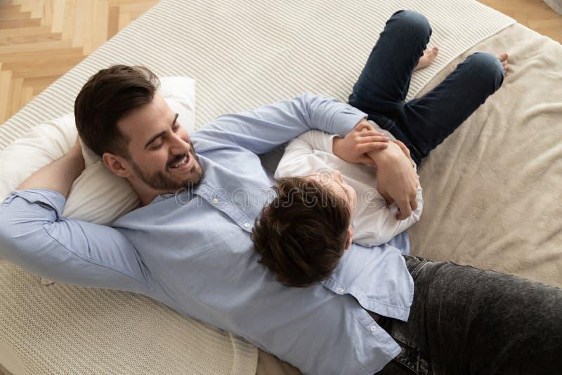 Papa heureux se trouvant sur le lit parlant avec peu de fils image stock