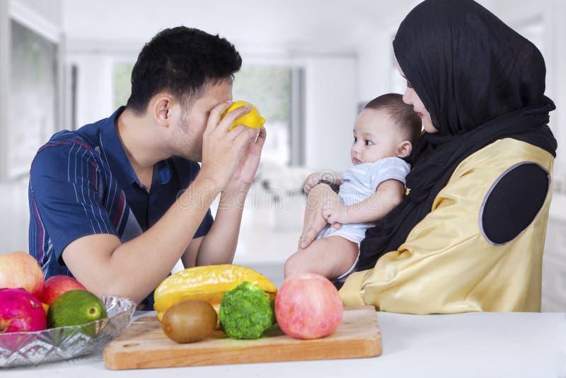 Papa jouant avec son bébé employant les fruits oranges image libre de droits