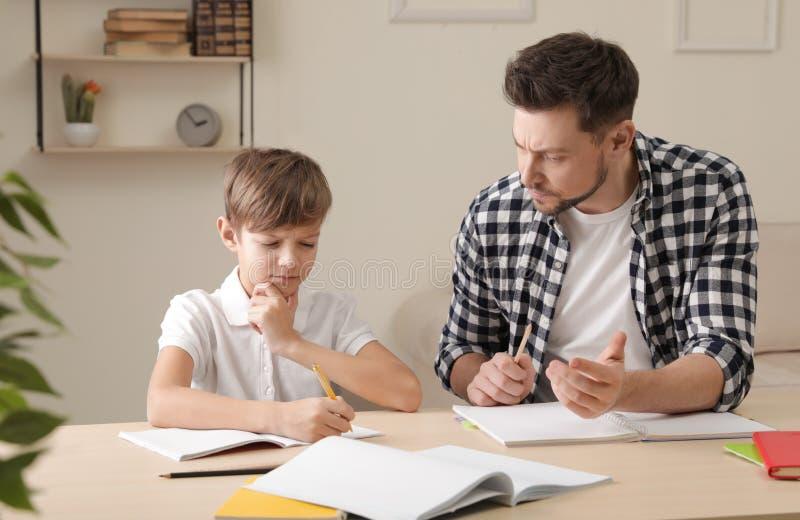 Papa luttant pour aider son fils avec la t?che d'?cole photo stock
