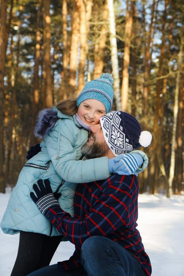 Papa met zijn dochter in de winter in het bos stock fotografie