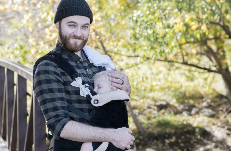 Papa millénaire avec le bébé dans la marche extérieure de transporteur photos libres de droits