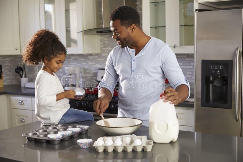 Papa noir et jeune fille faisant cuire au four ensemble dans la cuisine image libre de droits