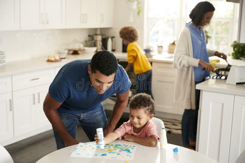 Papa observant son fils d'enfant en bas âge peindre un tableau se reposant à une table dans la cuisine, alors que la mère et la f images libres de droits
