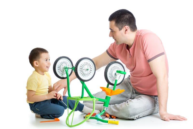 Papa réparant la bicyclette d'enfants avec son fils, photo stock