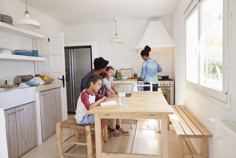 Papa s'asseyant avec des enfants à la table de cuisine tandis que la maman fait cuire photo libre de droits