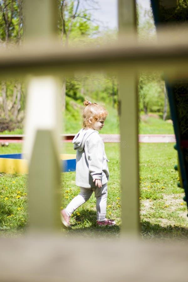 Papa stil als een weinig gelukkige rode dochter wordt gefotografeerd, die onder de warme de lentezon zonnebaden op de speelplaats stock fotografie