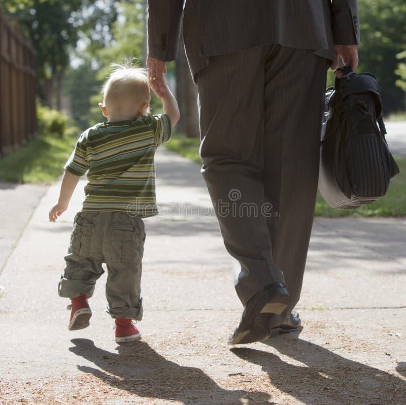 Papa travaillant marchant avec le fils images stock