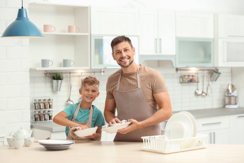 Papa und Sohn, die das Geschirr abwischen lizenzfreie stockbilder