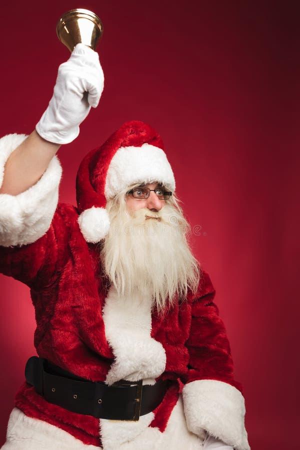 Papai Noel assentado soa seu sino e olha para tomar partido fotografia de stock