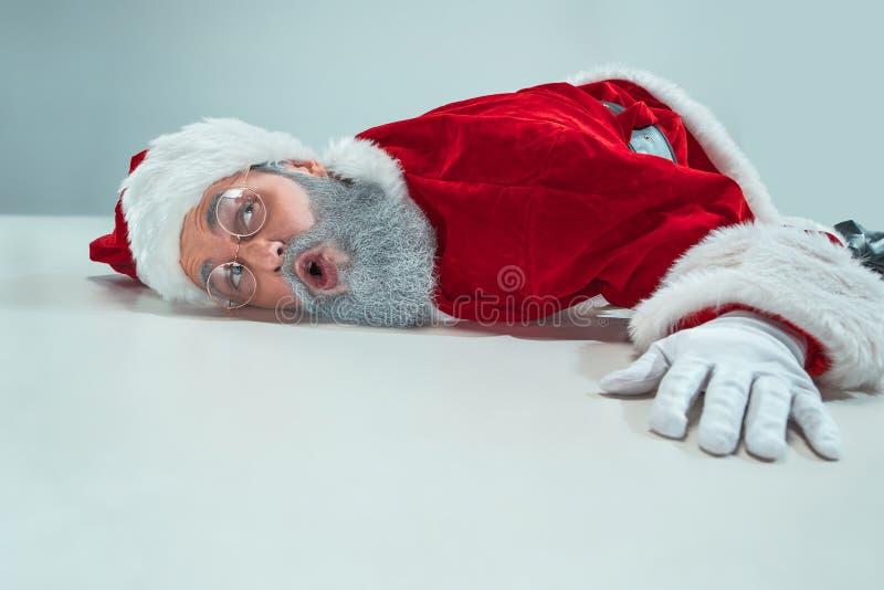 Papai Noel branco vermelho sobrecarregou o conceito da neutralização da frustração que encontra-se no assoalho isolado no fundo b fotos de stock royalty free