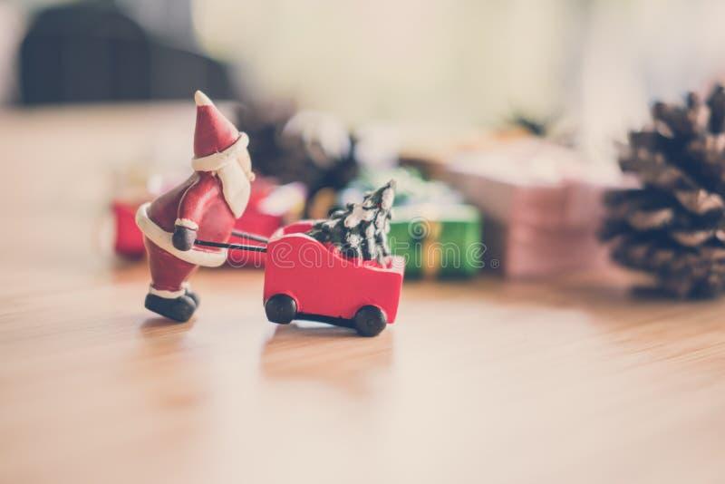 Papai Noel com a árvore do Xmas no carrinho de mão aterra o minia do trole foto de stock royalty free