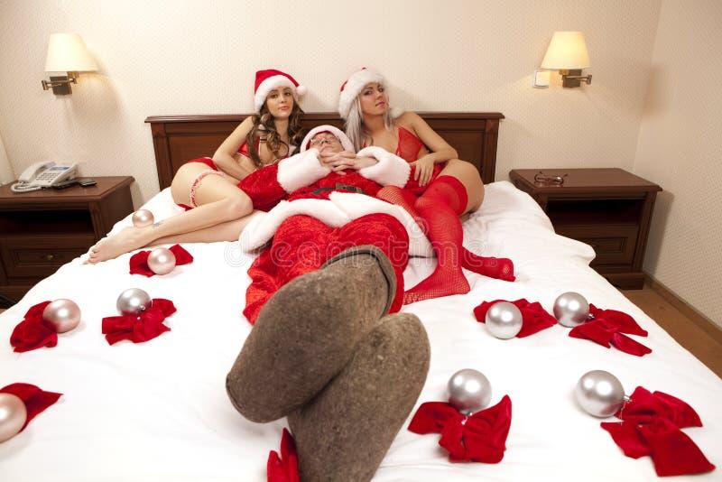Papai Noel com as duas meninas 'sexy' fotos de stock royalty free