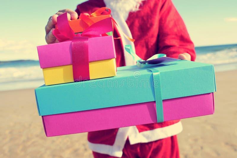 Papai Noel com os presentes na praia imagens de stock