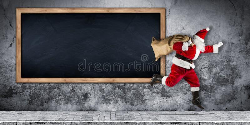 Papai Noel com pressa com o saco completo dos presentes que correm o salto fotografia de stock