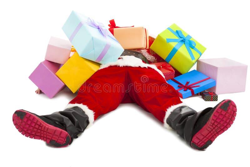 Papai Noel demasiado cansado para encontrar-se no assoalho com muitas caixas de presente imagens de stock