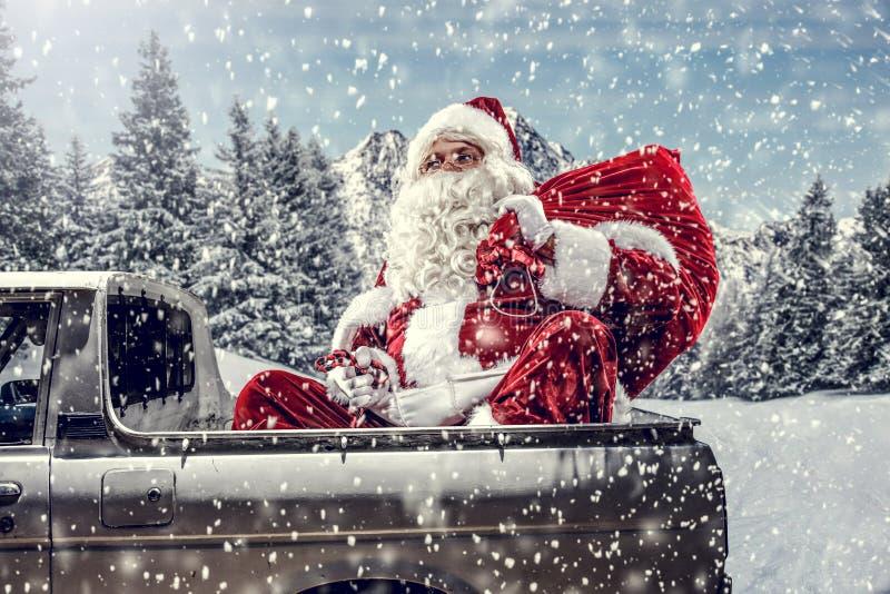 Papai Noel em um carro dirigindo para entregar presentes de natal num dia ensolarado de inverno Suborno da floresta de montanha d imagem de stock royalty free