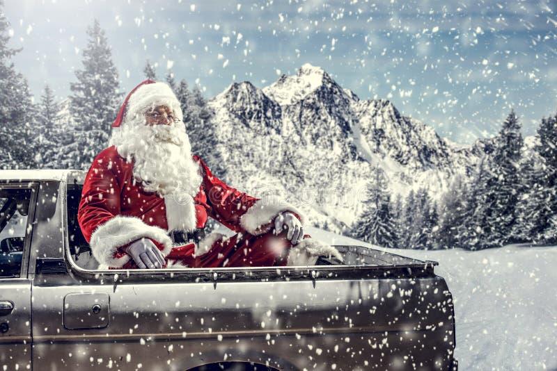 Papai Noel em um carro dirigindo para entregar presentes de natal num dia ensolarado de inverno Suborno da floresta de montanha d imagem de stock