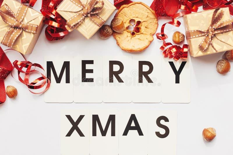 Papai Noel em um sledge Caixas de presente com fita, as avelã e fatia vermelhas de maçã secada sobre o fundo branco fotos de stock
