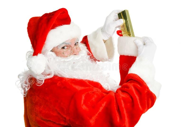 Papai Noel enche uma meia do Natal fotos de stock