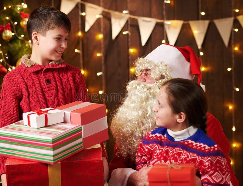 Papai Noel, menino e menina se posando em casa perto de uma árvore de Natal decorada com luzes, eles conversam, sorriem e imagens de stock royalty free