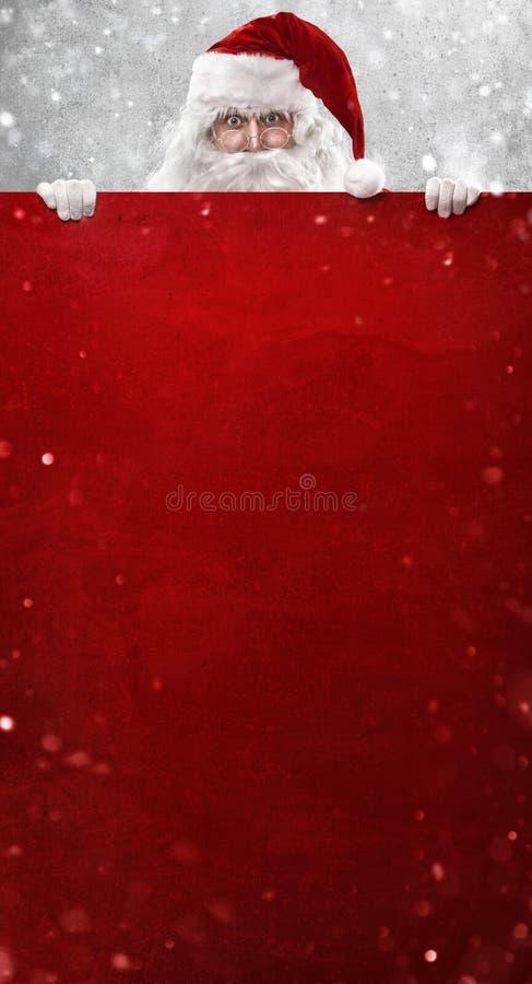 Papai Noel mostrando algo em uma parede vermelha fotos de stock royalty free