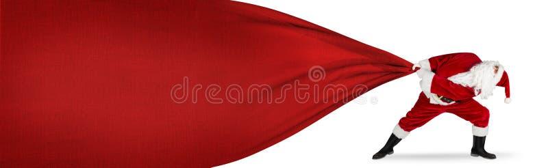 Papai Noel na luta impossível para puxar o saco vermelho grande enorme do presente fotos de stock royalty free