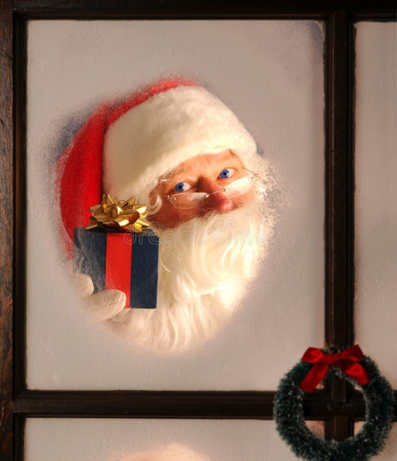 Papai Noel no indicador com presente imagem de stock royalty free