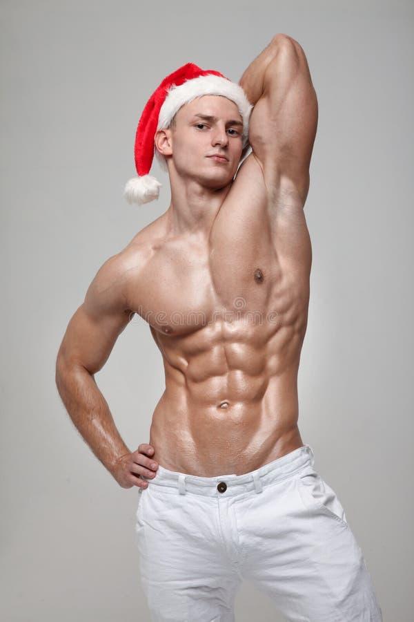 Papai Noel _2 O indivíduo muscular novo que veste o chapéu de Santa Claus demonstra seus músculos foto de stock royalty free