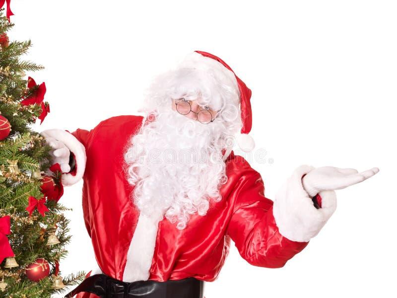 Papai Noel perto de apontar da árvore de Natal. fotografia de stock