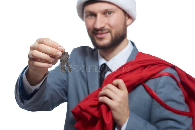 Papai Noel que dá a chave da casa gosta do presente foto de stock