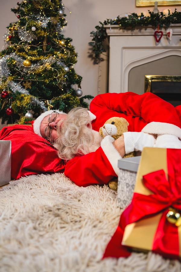 Papai Noel que dorme na encolho de ombros com urso de peluche fotografia de stock royalty free