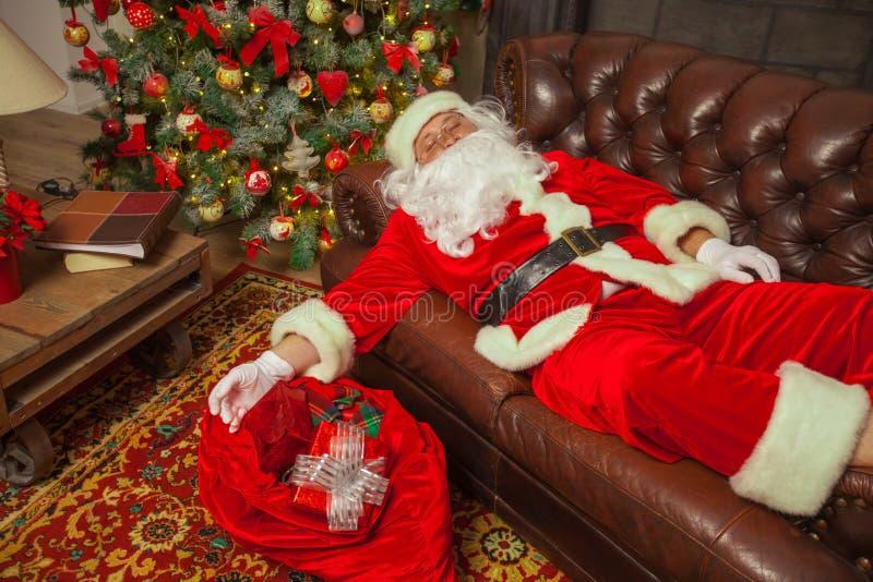 Papai Noel que dormita em uma sala de visitas decorada com saco completamente imagens de stock