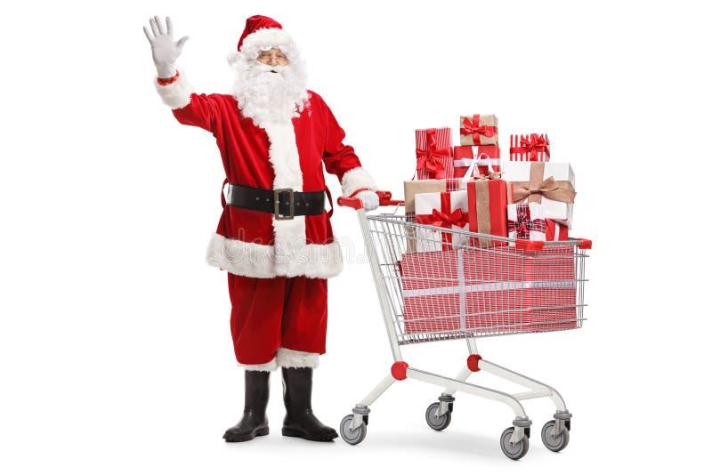 Papai Noel que está com um carrinho de compras completamente dos presentes e da ondulação imagens de stock royalty free