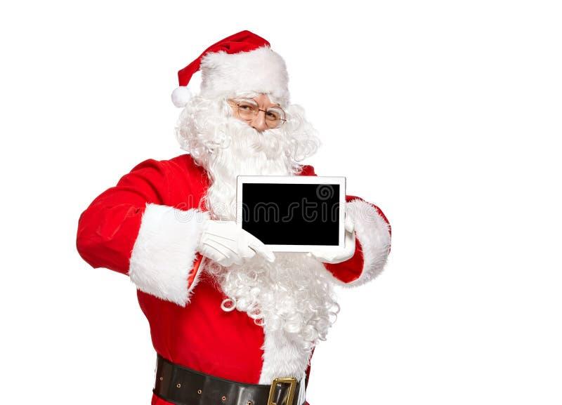 Papai Noel que guarda um tablet pc fotos de stock royalty free