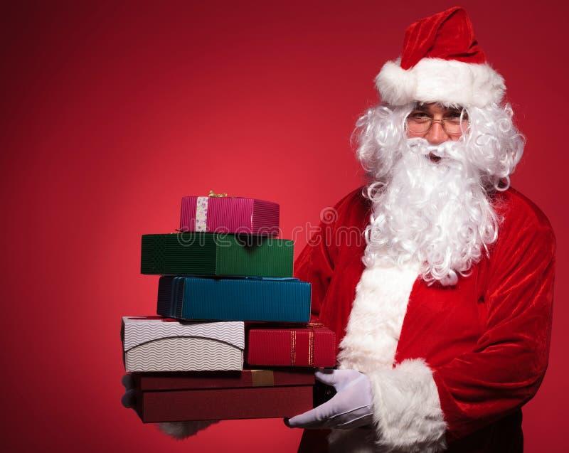 Papai Noel que guarda uma pilha grande dos presentes fotografia de stock