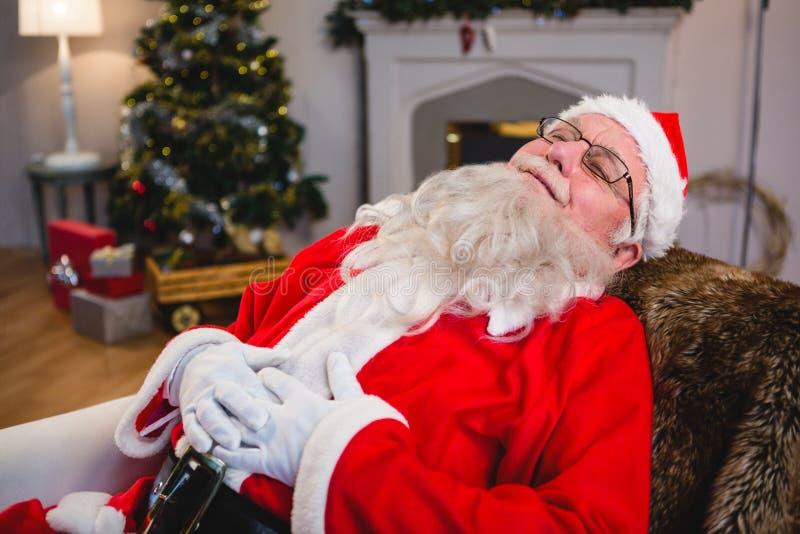 Papai Noel que relaxa no sofá na sala de visitas em casa imagem de stock royalty free