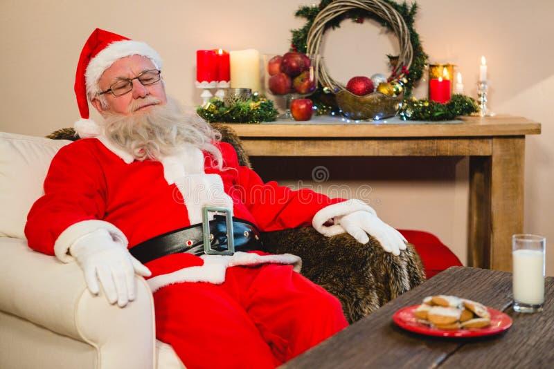 Papai Noel que relaxa no sofá na sala de visitas em casa foto de stock
