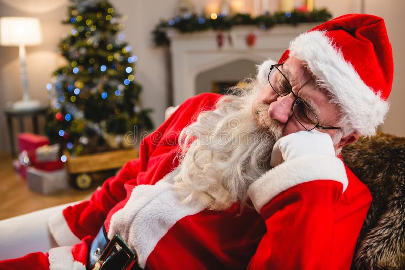 Papai Noel que relaxa no sofá na sala de visitas em casa imagem de stock