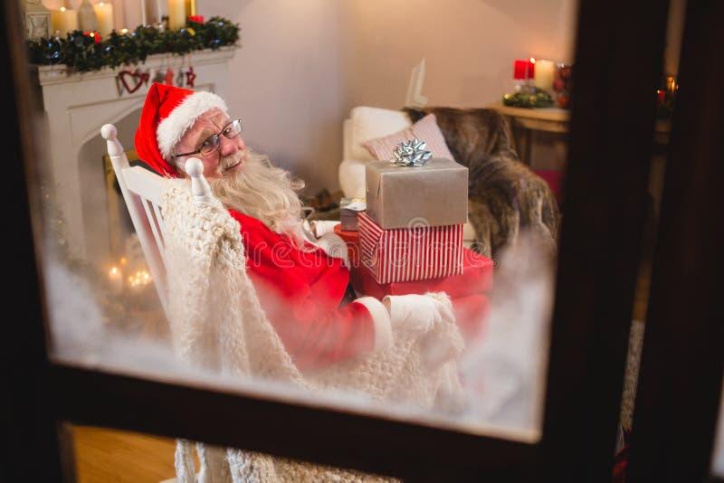 Papai Noel que senta-se com a pilha de caixas de presente na sala de visitas durante o tempo do Natal fotos de stock royalty free