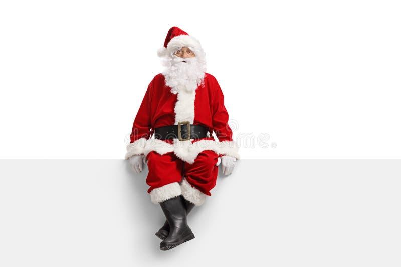 Papai Noel que senta-se em uma bandeira branca foto de stock