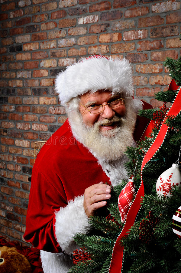 Papai Noel que sorri pela árvore de Natal foto de stock